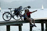 Germany, Bavaria, Couple with mountain bikes taking a break on landing stage