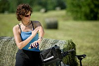 Germany, Bavaria, Seeshaupt, Woman with mountain bike applying sun cream (thumbnail)