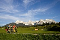 Germany, Bavaria, Mittenwald, Two women mountain biking across highway