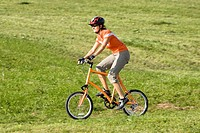 Germany, Bavaria, Oberland, Woman mountain biking across field