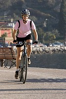 Italy, Trento, Riva del Garda, Female mountainbiker riding across pier