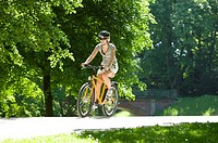 Germany, Bavaria, Munich, Woman mountain biking across park