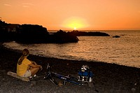 Spain, The Canary Islands, La Palma, Woman with mountain bike relaxing at sunset