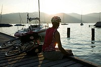 Germany, Bavaria, Tegernsee, Woman with mountainbike taking a break on landing stage
