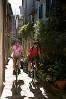 Italy, Tuscany, Poggio, Mountainbikers riding an alleyway