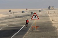 Spain, The Canary Islands, Man mountain biking on highway, traffic sign, slippery road