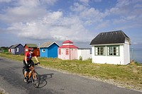 Denmark, Woman mountain biking alongside frame houses