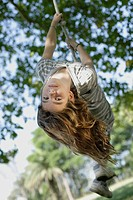 Girl swinging on rope swing