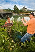 Fisherman poses with King Salmon at Ship Creek in downtown Anchorage, Alaska during Summer