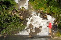 Fisherman spin fishing for salmon at the base of Fisher Falls at Big River Lakes in Redoubt Bay State Critical Habitat Area, Southcentral Alaska