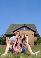 Fröhliche Familie sitzend vor Eigenheim