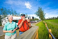Senior couple photographs birds from a viewing deck at Creamer´s Dairy near Fairbanks. Summer in Interior Alaska