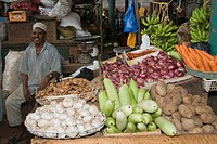 Vendor at stall with vegetables, vegetable market, Mombasa, Kenya