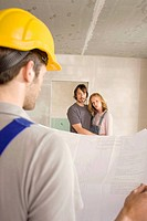 Construction worker holding construction plan, young couple in background