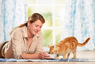 woman feeding domestic cat / restrictions: Tierratgeber_Bücher / animal guidebooks