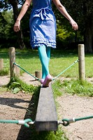 Woman walking on a plank in playground