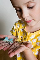 Girl holding toy butterflies