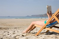 Woman reading a book on an empty beach