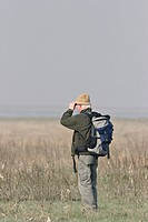 HIKING Somme bay in Oise in Picardy, France. Walker observing the scenery and the fauna probably birds.