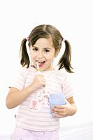 Portrait of a cheerful young girl brushing teeth