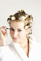 Young woman with curlers and mascara