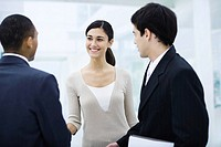 Professional woman standing with two businessman, shaking one man´s hand, smiling