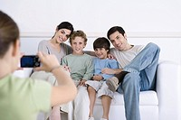 Young girl taking photo of her parents and brothers sitting together on sofa