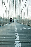 Jogger running across pedestrian walkway of Brooklyn Bridge in New York City, Manhattan skyline in distance