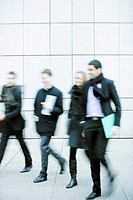 Business associates walking together down sidewalk