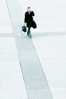 Businessman walking across public square talking on cell phone (thumbnail)