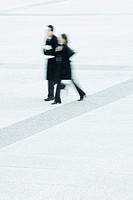 Businessman and businesswoman walking together across public square