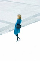 Woman in blue overcoat descending stairs
