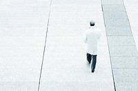 High angle rear view of business man walking down sidewalk
