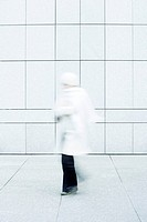 Woman wearing white coat, white knit hat and white knit scarf walking down sidewalk