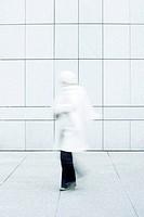 Woman wearing white coat, white knit hat and white knit scarf walking down sidewalk
