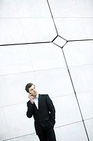 Businessman using cell phone, hand in pocket, casually standing by wall