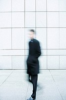 Businessman hurrying down sidewalk (thumbnail)