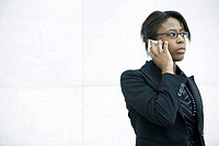 Businesswoman using cell phone, looking away