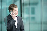 Businessman using cell phone, looking away