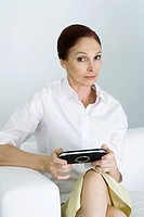 Mature woman holding handheld video game, looking at camera with eyebrow raised