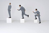 Identical businessmen climbing gradually larger blocks