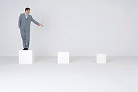 Businessman standing on pedestal, presenting empty pedestals