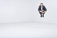 Businessman jumping in midair, shouting at camera