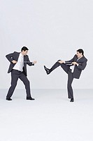 Businessman having tug-of-war with self (thumbnail)