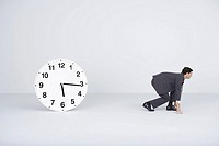 Businessman crouching, ready to run, next to clock
