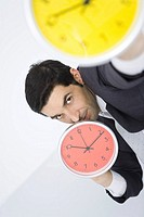 Businessman holding up clocks, looking at camera
