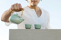 Man holding teapot, cropped, mid section