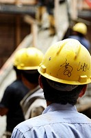 Construction workers with yellow hard hats from behind