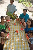 Families eating watermelon at picnic table