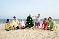 Friends decorating Christmas tree on beach